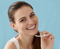 girl smiling holding invisalign