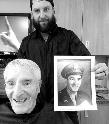 Barber of Gentlemens Club holding up Veterans photo as a young man