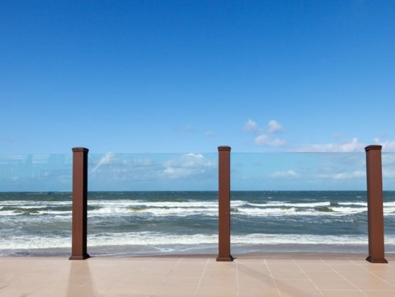 glass fencing with wooden posts leading with waves crashing on the beach behind them
