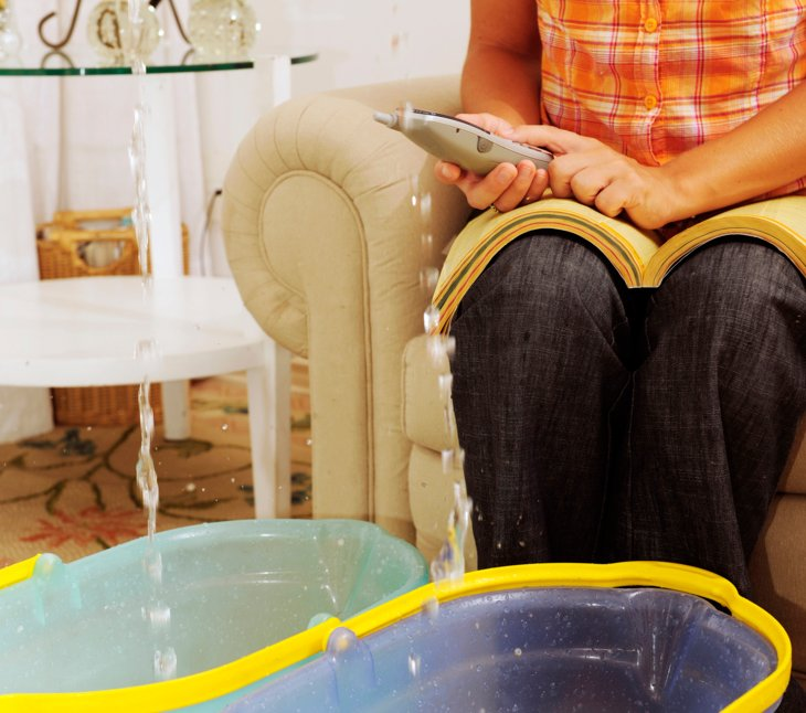woman phoning plumbercoleraine for their emergency plumbing service  as rain drips into buckets