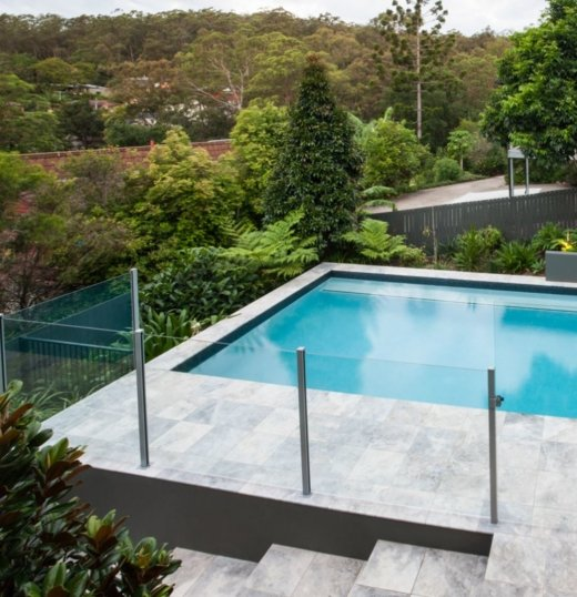 Angled photo of a pool with a glass pool fence with metal poles in between the fixtures