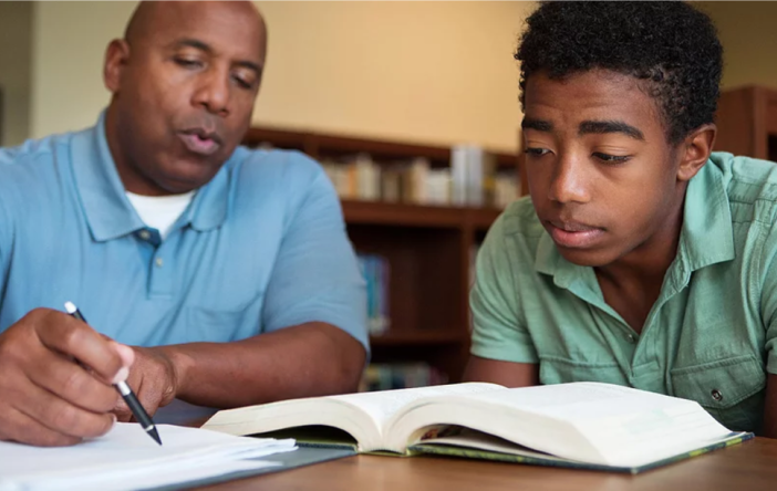 An adult male tutor working with a young adult male Dorson Scholar